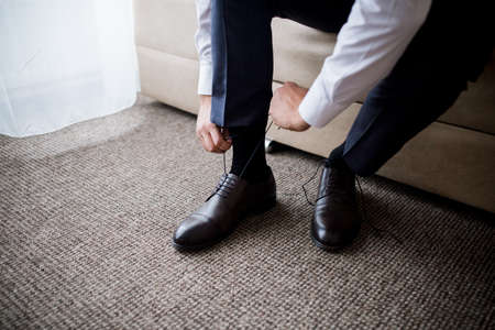 man ties the laces in his shoes in the morning in the room