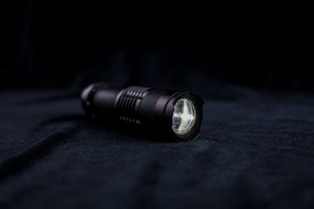 a tactical flashlight on black background shines