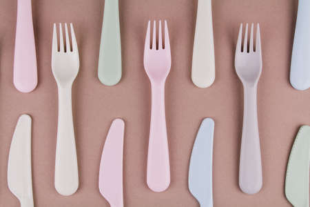 a set of plastic cutlery in different colors spoons forks knives on the kitchen table and eco-friendly plastic