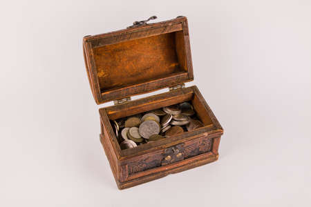 old wooden chest with a many different coins