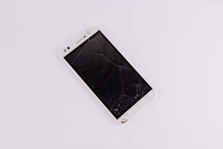 a smartphone with broken screen on white background