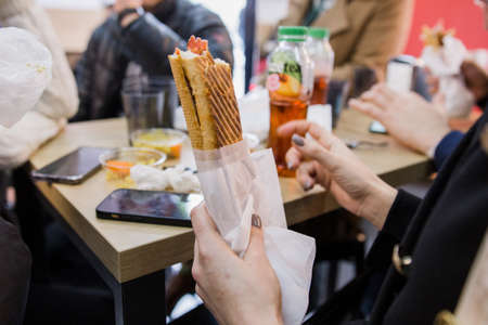 man holding a sandwich in his hand in a restaurant