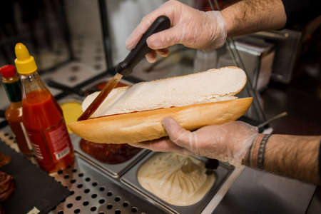 the cook spreads the sauce on the baguette with knife Standard-Bild