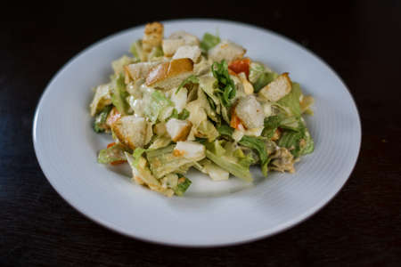 a caesar salad in a white plate in the kitchen