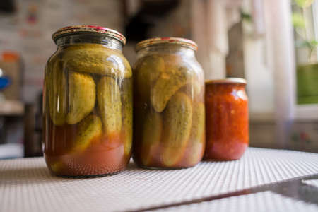 a canned cucumbers in a jar on the kitchen table Standard-Bild