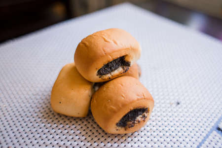 a buns with poppy seeds on the table in the kitchen Standard-Bild