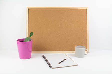 a cork board for notes on white background with pen and notepad in office