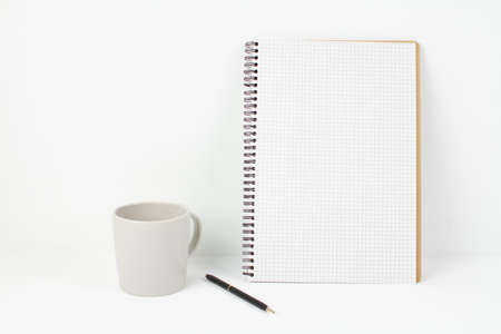 a pen with notepad and cup on white background in office Banque d'images