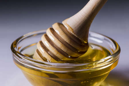a fresh golden honey pours beautifully from a wooden honey spoon