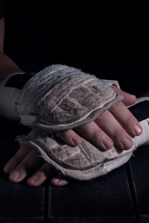 Close up of hands of martial fighter with boxing equipment donned. Ready to fight concept.