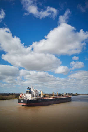 Campana River, Buenos Aires, Argentina - 22 August 2018: Big bulk carrier ship passing Campana River on her way to one of local ports on beautiful background with pretty looing clouds and sky.