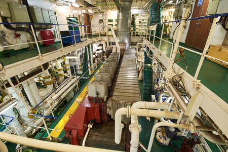 Panoramic view of main engine on a merchant ship in the engine room with all the piping, generators, turbins, etc.