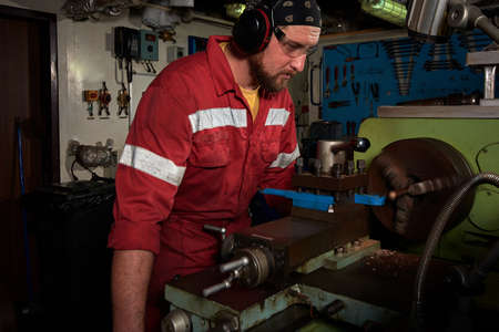 Worker in red uniform operating in manual lathe in metal big workshop with dark environment.