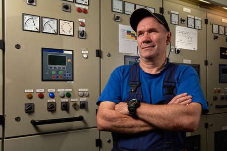 Proud and happy mechanic / chief engineer, posing with his arms crossed, smiling, donned in uniform in the engine room of an industrial cargo ship.