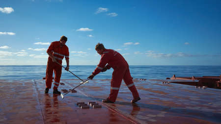 At sea, Atlantic Ocean - Circa November 2018: Ships crew members painting hatch cover outdoors with bright blue sky on a background. Ship maintenance concept. Teamwork concept.