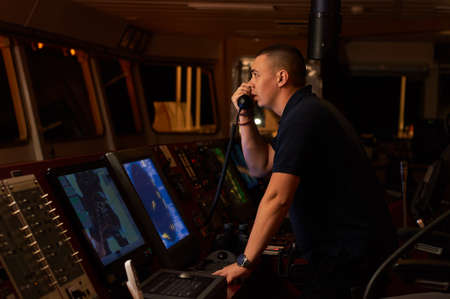 Navigation officer. Pilot on a bridge of a vessel underway with radio station and binocular in hands Stock Photo