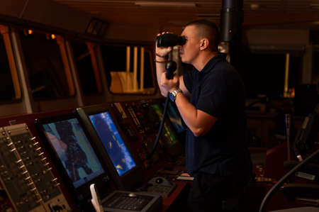 Navigation officer. Pilot on a bridge of a vessel underway with radio station and binocular in hands Фото со стока