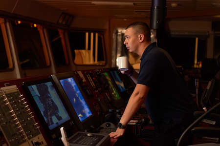 Navigation officer. Pilot on a bridge of a vessel underway with radio station and binocular in hands