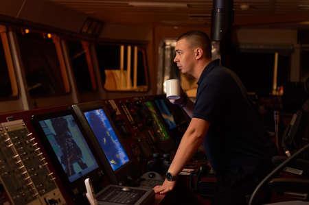 Oficial de navegación. Piloto en un puente de un buque en marcha con estación de radio y binoculares en las manos Foto de archivo