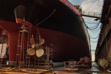 View of ship propeller and rudder in a dry dock background. Transportation industry. Freight transportation. Ship repair and maintenance concept.
