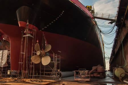 Vista dell'elica e del timone della nave in un fondo del bacino di carenaggio. Industria dei trasporti. Trasporto merci. Riparazione navale e concetto di manutenzione.