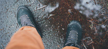 Man staingg during rainy autumn weather in a puddle in a waterproof tracking shoes. Fall weather Concept. All season adventure concept. Muddy background fo any fall article.
