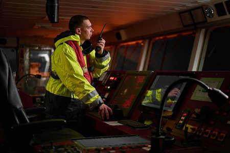 Navigator. Pilot, Kapitän als Teil der Schiffsbesatzung, die tägliche Aufgaben mit UKW-Funk, Fernglas, Logbuch erfüllt, in der Nähe von ECDIS und Radarstation an Bord eines modernen Schiffes mit hochwertiger Navigationsausrüstung auf der Brücke stehen. Großartiges Design für Navigation, Sicherheit der Schifffahrt, Güterbeförderungszwecke.