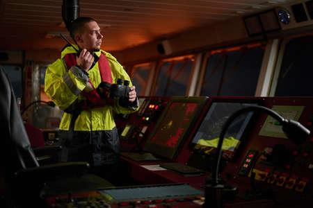 Navegador. piloto, capitán como parte de la tripulación del barco que realiza tareas diarias con radio VHF, binoculares, cuaderno de bitácora, cerca del ECDIS y la estación de radar a bordo de un barco moderno con equipo de navegación de alta calidad en el puente. Gran diseño para navegación, seguridad de envío, transporte de carga. Foto de archivo