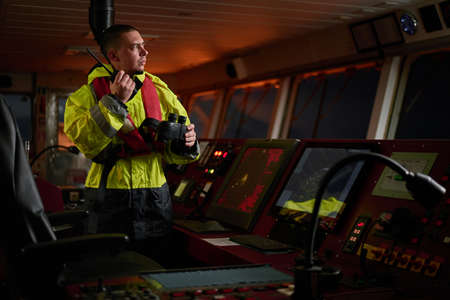 Navigator. pilot, captain as part of ship crew performing daily duties with VHF radio, binoculars, logbook, standing nearby to ECDIS and radar station on board of modern ship with high quality navigation equipment on the bridge. Great design for navigation, safety of shipping, cargo carriage puproses. Reklamní fotografie