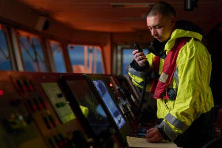 Navigator. Pilot, Kapitän als Teil der Schiffsbesatzung, die tägliche Aufgaben mit UKW-Funk, Fernglas, Logbuch erfüllt, in der Nähe von ECDIS und Radarstation an Bord eines modernen Schiffes mit hochwertiger Navigationsausrüstung auf der Brücke stehen. Großartiges Design für Navigation, Sicherheit der Schifffahrt, Güterbeförderungszwecke. Standard-Bild