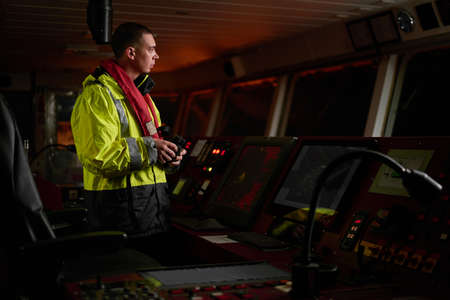 Navigator. pilot, captain as part of ship crew performing daily duties with VHF radio, binoculars, logbook, standing nearby to ECDIS and radar station on board of modern ship with high quality navigation equipment on the bridge. Great design for navigation, safety of shipping, cargo carriage puproses.