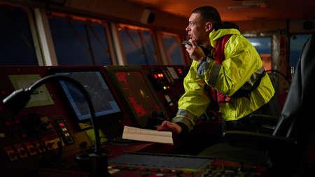 Navigatore. pilota, capitano come parte dell'equipaggio della nave che svolge compiti quotidiani con radio VHF, binocolo, giornale di bordo, in piedi vicino a ECDIS e stazione radar a bordo di navi moderne con apparecchiature di navigazione di alta qualità sul ponte. Ottimo design per la navigazione, la sicurezza della spedizione, il trasporto merci.
