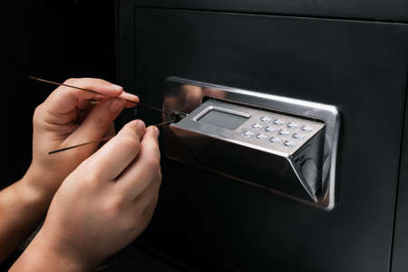 Close-up of Thief's hands attempting to Break Home Money Safe and perform Robbery. Safety and Home Security concepts.