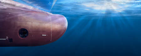 Big cargo ship sailing in the sea to International Shipping container terminal. Close up image detail ships bow, underwater view. Shipping business and underwater survey concept. Hull maintenance and inspection.