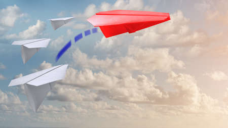 A group of white paper air planes heading in one direction and one red individual pointing in the different way as a business industry icon for innovative solution. 版權商用圖片