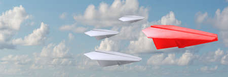 Business concept: A group of white paper air planes heading in one direction lead by red individual paper plane as a business industry icon for leadership, teamwork and management concept.
