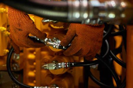 Photo discrète de l'entretien des tuyaux hydrauliques sur une machine de l'industrie lourde dans un garage.