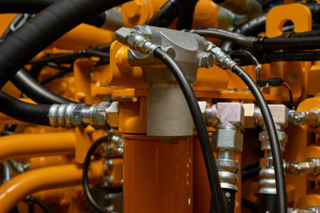 Close up view of hydraulic pipes of heavy industry machine. Low key. Hydraulic maintenance concept. Standard-Bild