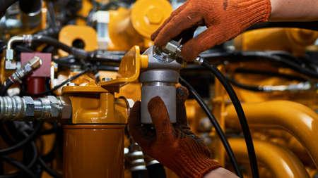 Foto de bajo perfil de mantenimiento de tuberías hidráulicas en máquinas de la industria pesada en un garaje. Foto de archivo