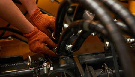 Foto de bajo perfil de mantenimiento de tuberías hidráulicas en máquinas de la industria pesada en un garaje.