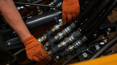 Low key photo of hydraulic pipes maintenance on heavy industry machine in a garage. Stock Photo