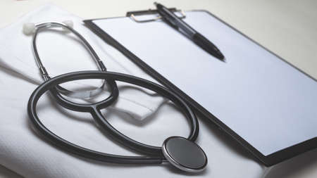 Stethoscope and note board on white background.
