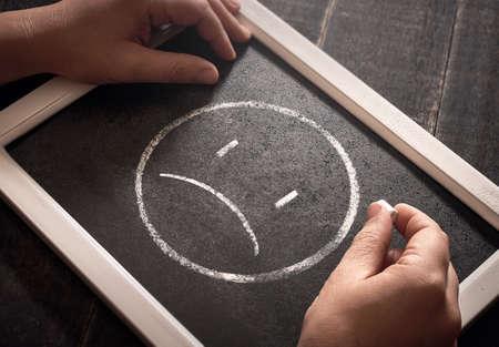 Hand drawing sad smiley face on black chalk board. 版權商用圖片