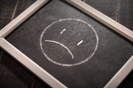 Hand drawing sad smiley face on black chalk board. Negative human emotion face expression.