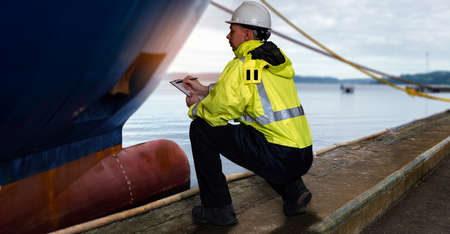 Ship supervisor engineer inspector stands at the dockside in a port. Wearing safety helmet and yellow vest. Cargo shipping industry. Protection and idemnity concept.