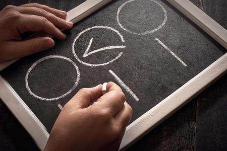 Blackboard with check boxes on chalk board. Hand writing. Dark background. 版權商用圖片