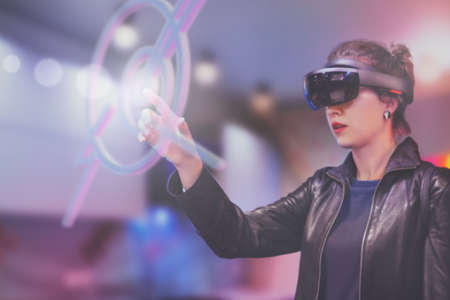 Portrait of young Caucasian woman using augmented and virtual reality with holographic hololens glasses. Pink, magenta and blue blurred background. Future technology concept.