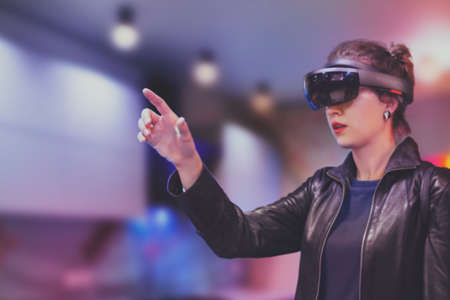 Portrait of young Caucasian woman using augmented and virtual reality with holographic hololens glasses. Pink, magenta and blue background. Future technology concept. 免版税图像