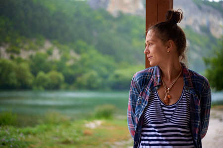 Beautiful happy smiling wet woman during rainy day staying near the lake in mountains. Lifestyle concept.