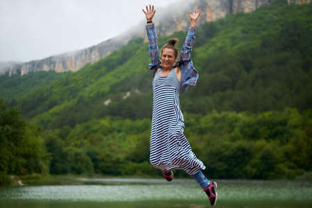 Casual dressed hiking woman under the rain jumping near the lake in mountains. Candid and authentic expression.